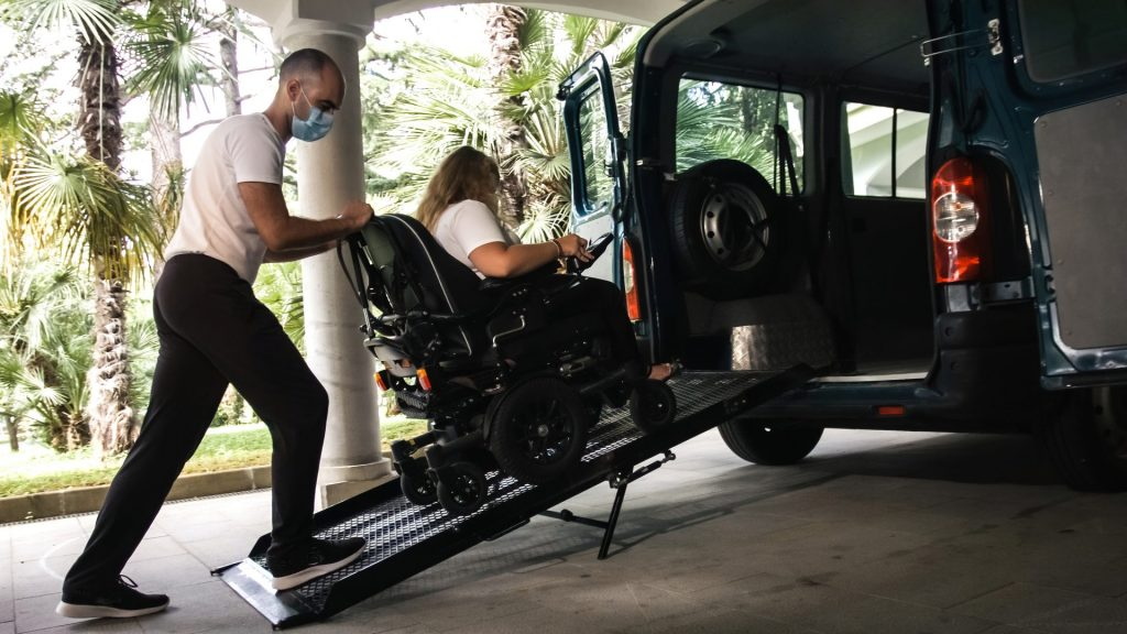 Wheelchair Users being Helped Into An Adapted Vehicle